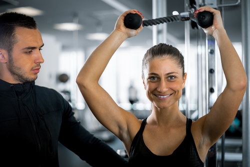 Personal fitness trainer with his client in gym.