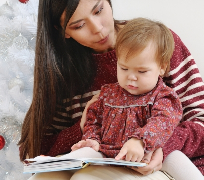 portrait of cute little baby girl reading book with her mother n